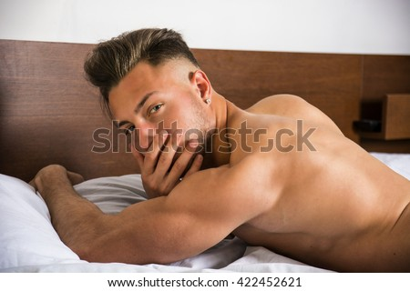 Naked sexy young man with muscular body on bed looking away - stock photo
