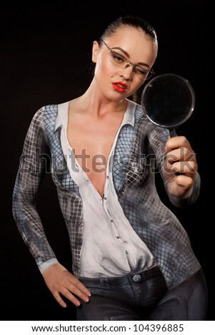 Naked shocked woman covered with body paint business suit, holding a magnyfing glass. Concept image of sexual issues at work. High resolution studio picture on black background. - stock photo