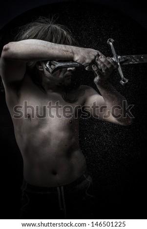 naked warrior carrying steel sword - stock photo