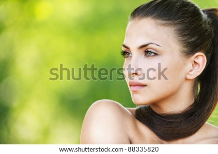 naked woman beautiful dark-haired serious looking direction background green summer park