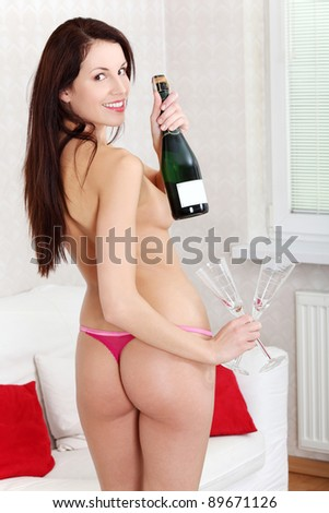 Naked woman holding champagne and two glasses. - stock photo