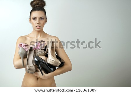 Naked woman holding many pairs of shoes - stock photo