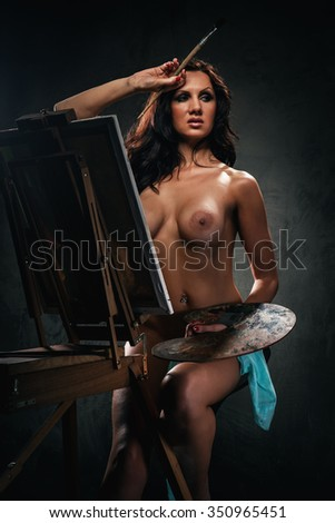 Naked woman painting, studio shot  - stock photo