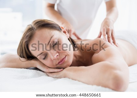 Naked woman receiving back massage from masseur at spa