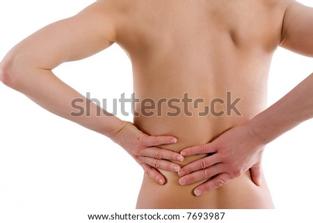 Naked woman's body from behind - she holds her lower back - stock photo