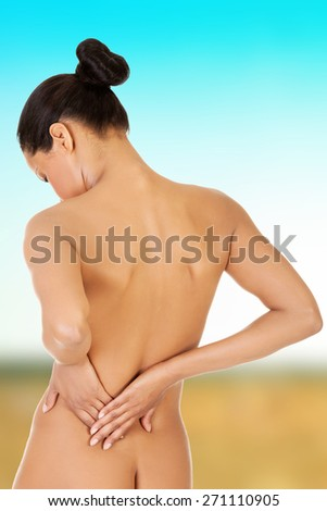 Naked woman touching her lower back. - stock photo