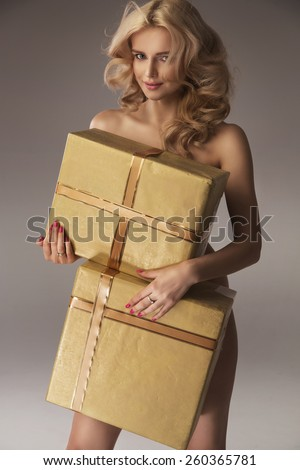 Naked woman with gift boxes - stock photo