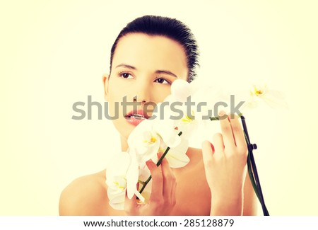 Naked woman with white orchid twig.