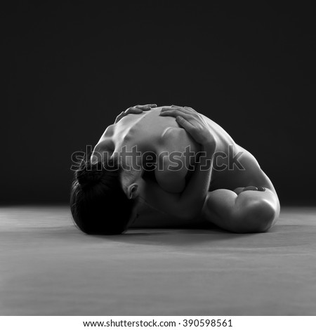 Naked yoga. Beautiful sexy body of young woman on gray background. Low key black and white studio photography - stock photo