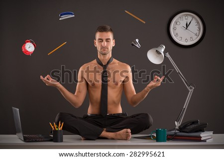 Naked yogi businessman relax in office, while his work is doing. Handsome businessman sit on table in office in lotus position and try to relax. - stock photo