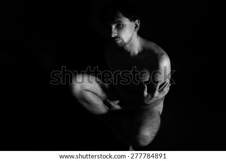 Naked young handsome man sitting on the floor - stock photo