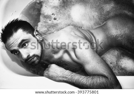 Naked young handsome man takes a bath