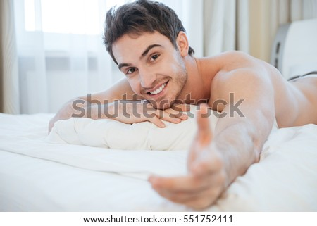 Naked young man lying on bed and looking at camera. Side view