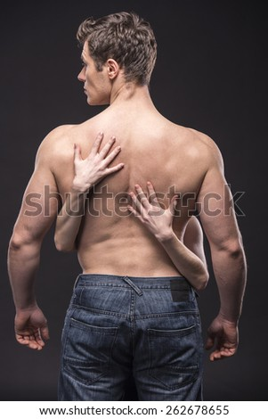 Naked young man with female hands on the back. - stock photo