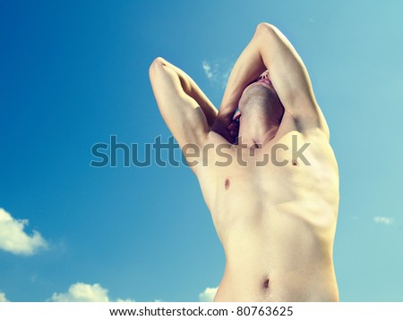 Naked young strong man against the blue sky - stock photo