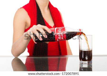 NAKHODKA, RUSSIA - JANUARY 18, 2014: Asian girl pours a Coca-Cola from a bottle into a glass. Coca-Cola is a carbonated soft drink sold in stores, restaurants, and vending machines worldwide. - stock photo