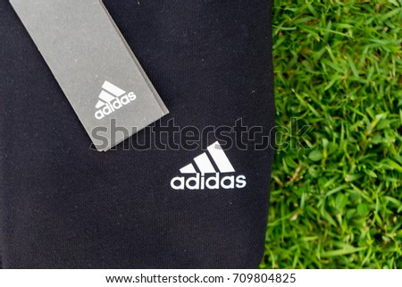 NAKHON PATHOM, THAILAND - SEPTEMBER 2, 2017:A logo adidas on sports jacket and sweatpants,  A German multinational corporation that designs and manufactures sports shoes, clothing and accessories