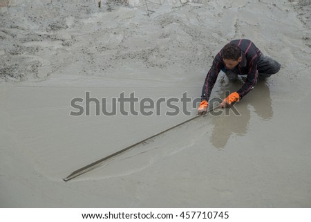 NAKHON RATCHASIMA -JULY 6 : Plasterer screed concrete for floor at construction on July 6, 2016 in Nakhon Ratchasima, Thailand