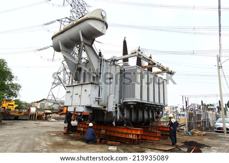 NAKHON SAWAN-THAILAND -NOVEMBER 11 : The construction of electrical substation with workers transported a large old transformer, November 11, 2013 in Nakhon Sawan province, Thailand - stock photo