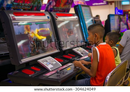Nakhon Si Thammarat, 27 june 2015: Boys play fighting game on arcade machine in Tesco Lotus supermarket at Nakhon Si Thammarat, Nakhon Si Thammarat province, Thailand. - stock photo