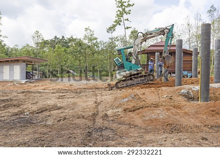 NAKHON SRI THAMMARAT, THAILAND - MAY 10: Thai construction site worker watching excavator bucket digger digging on new construction site on May 10, 2015 in Nakhon Sri Thammarat, Thailand. - stock photo