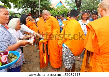 NAKHONSAWAN, THAILAND - OCT 20 : Unidentified Buddhist monks are given food offering from people in the morning for End of Buddhist Lent Day. on October 20, 2013 in Nakhonsawan, Thailand.