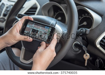 NAKORN PATHOM, THAILAND - FEB 12, 2016: A man hand holding screen shot of IP camera app showing on iPhone 6 in the car. - stock photo