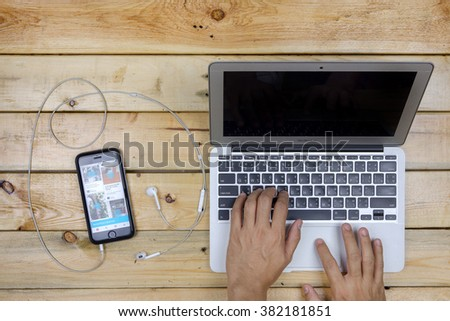 NAKORN PATHOM, THAILAND - FEB 17, 2016: A man use laptop and screen shot of Pinterest app showing on iPhone 6 on wooden table. - stock photo