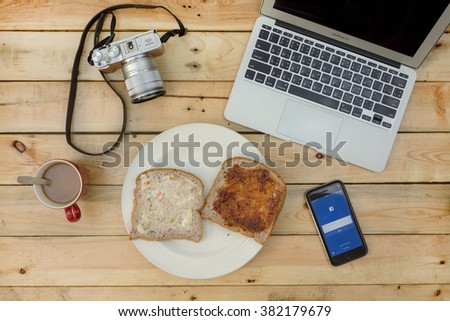 NAKORN PATHOM, THAILAND - FEB 18, 2016: laptop, camera, coffee, bread and screenshot of Facebook app on iPhone6 on wooden table. on wooden table. - stock photo