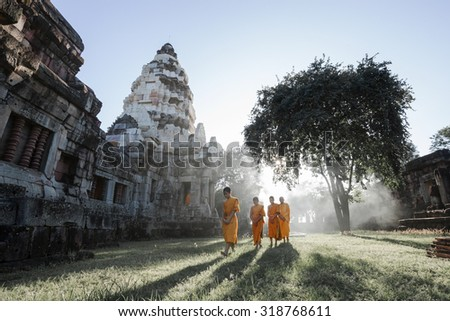 NAKORN RATCHASIMA - SEP 19: Unidentified Thai monks walking with sunlight at Phanomwan Historical Park on September 19, 2015 in Nakhon Ratchasima, Thailand - stock photo