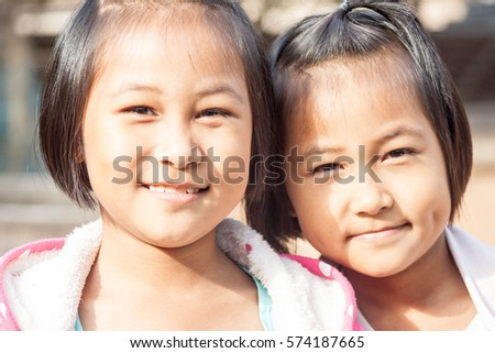 Nakornphanom province, Thailand, 30 January 2017: Cuties twin girls are smiling to photographer on sunny day.