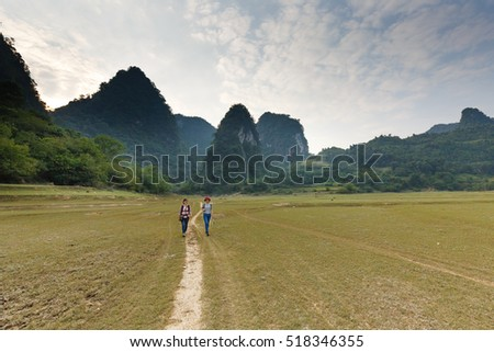 Nam Cha, Cao Bang province, Vietnam - September 22, 2016 : Two young girls traveling to explore wilderness lake Nam Cha. Scene here is spectacular with huge limestone mountains of Cao Bang, Vietnam