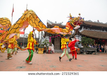 NAMDINH, VIETNAM-APRIL 14: A group of unidentified people perform dragon dance during Tet Lunar New Year celebrations on April 14, 2013 in Nam Dinh, Vietnam. This is a traditional cultural activity. - stock photo