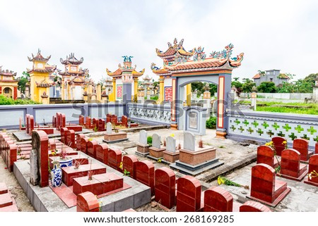 NAMDINH, VIETNAM - APRIL 5, 2015 - A typical tomb of the Vietnamese in a graveyard. As per tradition, tombs are built with Orient tops in Buddhist style and colorful.  - stock photo