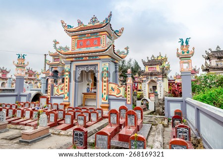 NAMDINH, VIETNAM - APRIL 5, 2015 - Tombs of the Vietnamese in a graveyard. As per tradition, tombs are built with Orient tops in Buddhist style and colorful.  - stock photo