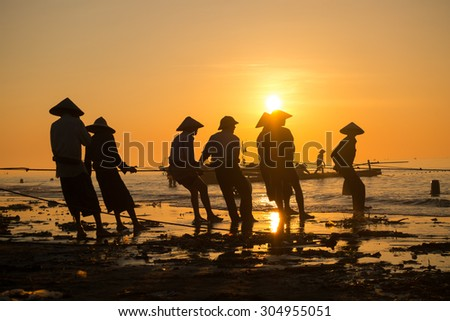 NAMDINH, VIETNAM, AUGUST 8, 2015,: Fishermen draw up a net to catch fishes on the beach in sunrise in Hai Ly, Nam Dinh. They go fishing at night and comeback in sunrise.