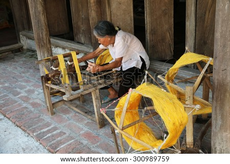 NAMDINH, VIETNAM - Jun 14, 2015: An elderly woman sitting roll of yellow silk with crude homemade instruments. This is the place preserved in a manner weaving tradition exists very little in VIETNAM
