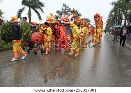 NAMDINH, VIETNAM - MARCH 02: A group of unidentified dancer with their colorful dragon during the traditional festival celebrations in the Tet Lunar New Year on March 02, 2015 in Nam Dinh.  - stock photo
