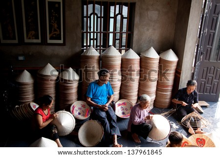 NAMDINH, VIETNAM - OCTOBER 23:  An unidentified group of people are producing conical hat on October 23, 2010  in Nam Dinh, Vietnam.  Conical hat is an traditional item of Vietnam. - stock photo