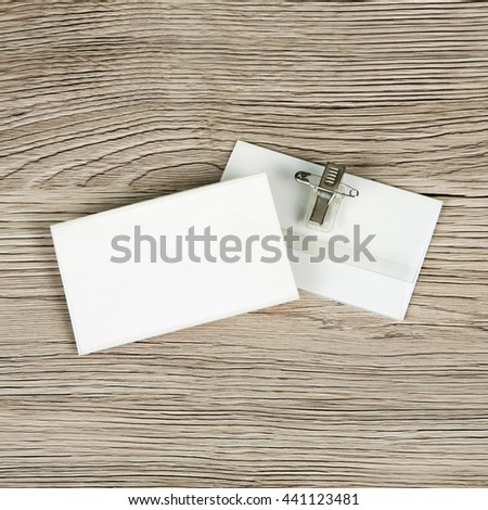 Name tag or identification holder with metal clip on wooden surface - stock photo