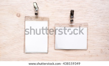 Name tag or identification holder with metal clip on wooden surface. Isolated on empty background. Slightly de-focused and close-up shot. Copy space.