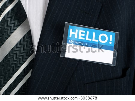 Namebadge saying hello on a well dressed businessman - insert your own information - stock photo