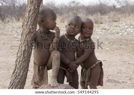 Namibia, Opuwo (October 10 - 2013) - Three young Himba children, doing nothing special. Himba is an ethnic group living in the north of Namibia.