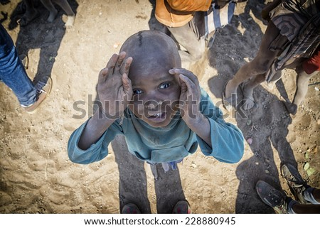 Namibia 24/08/2014: people from all over the world comes to Namibia to see the Himbas, one of the few tribes that still lives as in the past. Childs lives a simple life curious of the tourists. - stock photo