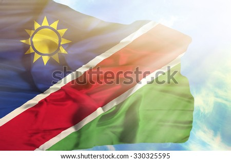 Namibia waving flag against blue sky with sunrays - stock photo
