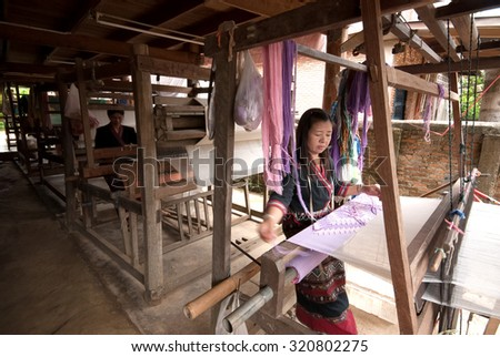 NAN ,THAILAND - SEPTEMBER 25.2013 : An unidentified Lua or Thin Hill Tribe woman is a  weaving by loom on a Hill Tribe village in Nan province, Northern of Thailand. - stock photo