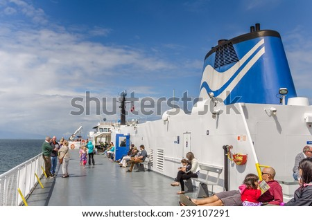 Nanaimo, Canada - June 29, 2014: Passengers on the sun deck of the BCF Ferry Queen of Oak Bay. BC Ferries provides all major passenger and vehicle ferry services in British Columbia. - stock photo