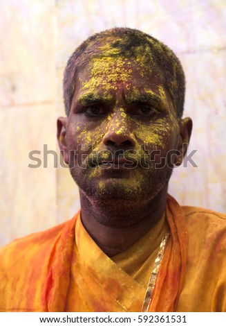NANDGAON, INDIA, 18 MARCH 2016 : Unidentified people with face smeared with colors participate in the holi celebration at Krishna temple, . Holi is the most celebrated religious festival in India.