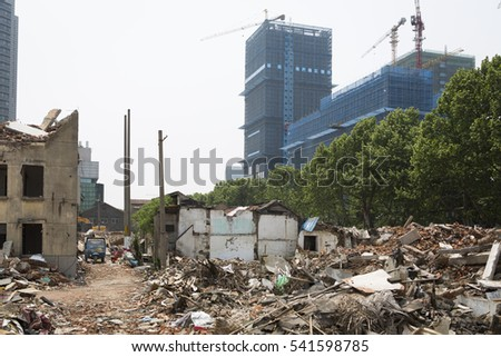 NANJING, CHINA - APRIL 29, 2016: Demolished houses with debris on the ground, for renovation building activity, new construction with cranes background.