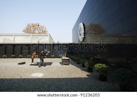 NANJING, CHINA - NOVEMBER 24: Visitors pray at the shrine of the Massacre Memorial Hall on Nov 24, 2011 in Nanjing, China. The hall commemorates the massacre of Nanjing by the Japanese army in 1937.